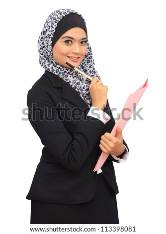 Beautiful young muslim business woman hold a pen and file, smiling to the camera. Islamic office attire dress. - stock photo