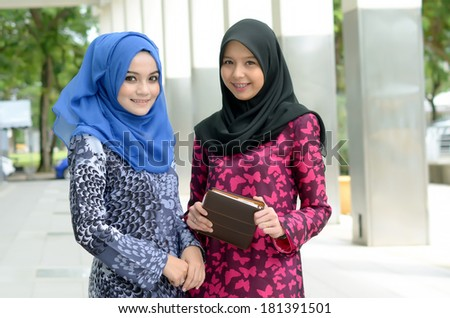 beautiful young muslim businesswoman sharing info together - stock photo