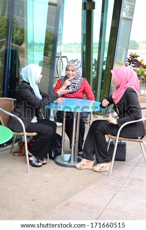 beautiful young muslim businesswoman sharing info together while drink at cafe