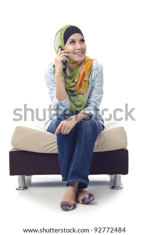 beautiful young muslim girl enjoy her conversation with friends using phone  isolated on white background - stock photo