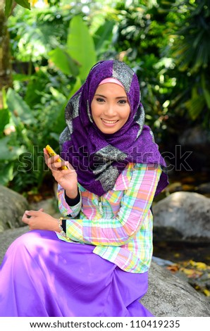 beautiful young Muslim girl sitting with mobile phone - stock photo