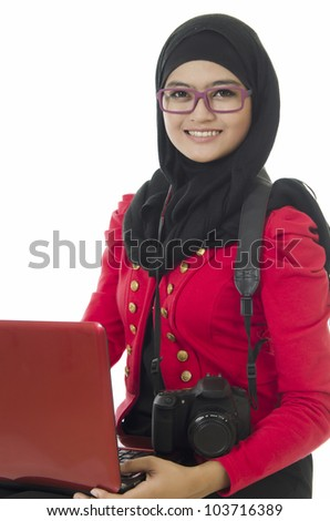 Beautiful young Muslim girl sitting with notebook and camera over white background. - stock photo