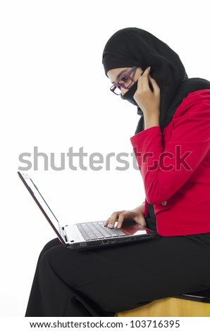 Beautiful young Muslim girl sitting with notebook over white background. - stock photo