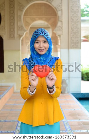 beautiful young muslim holding love case - stock photo