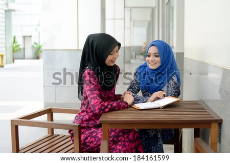 beautiful young muslim student sharing info together - stock photo