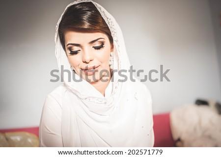 Beautiful young muslim woman. Bride preparing for wedding, wearing white hijab - stock photo