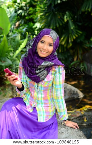 Beautiful young muslim woman in head scarf using phone