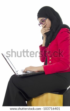 Beautiful young Muslim woman sitting with notebook over white background. - stock photo