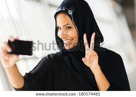 beautiful young muslim woman taking self portrait with smart phone - stock photo