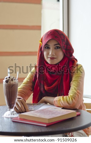 beautiful young muslim woman with lovely smiles having lunch at coffee shop - stock photo