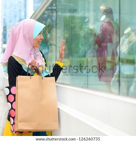 Beautiful young muslim woman with smile  while window shopping - stock photo