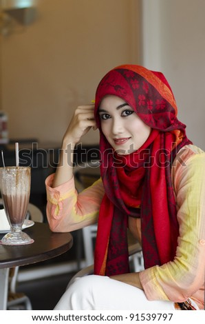 beautiful young muslim woman with stylish scarf smiling and enjoy chocolate drink in the coffee shop - stock photo
