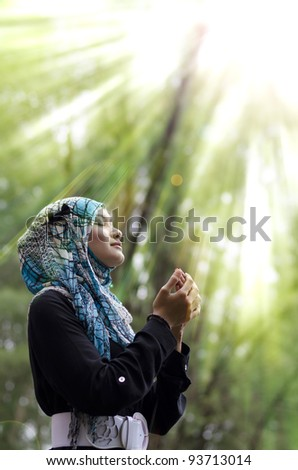 beautiful young muslimah woman with head scarf standing and praying under rays of light - stock photo