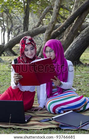 beautiful young muslimah women with head scarf looking the book at the recreation park - stock photo