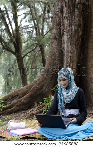 beautiful young muslimah women with head scarf spend her evening time with laptop at the recreation park - stock photo