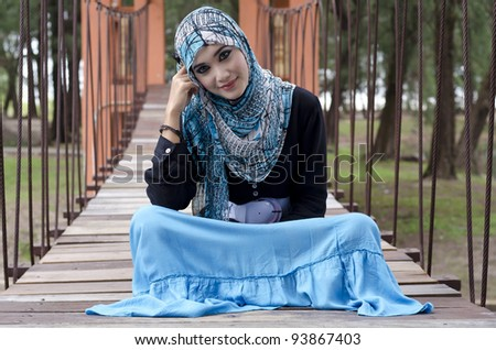 beautiful young muslimah women with stylish head scarf sit on the hanging bridge at recreation park - stock photo