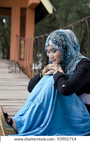 beautiful young muslimah women with stylish head scarf smiling sit on the hanging bridge at recreation park with close eyes - stock photo