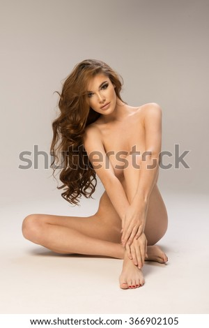 Beautiful young naked brunette woman sitting over the background  - stock photo