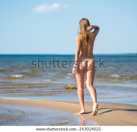 Beautiful young naked woman enjoying summertime at the beach - stock photo