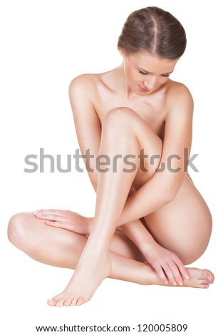 Beautiful young naked woman sitting on the floor - isolated on a white background - stock photo
