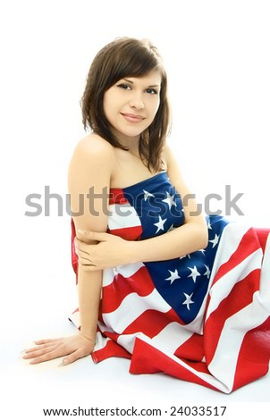 beautiful young nude woman sitting on the floor wrapped into the American flag - stock photo