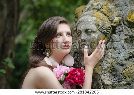 Beautiful young nude woman with an antique statue and bouquet of flowers. Comparison of lively female beauty and art of the ancient sculptors - stock photo