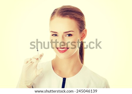 Beautiful young nurse or doctor with needle, shot ready to apply. - stock photo