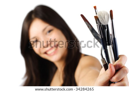 Beautiful young painter showing brushes. Shallow depth of field, focus on brushes. Isolated on white background. - stock photo