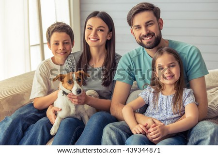Beautiful young parents, their cute little daughter and son are looking at camera and smiling, sitting with their cute dog on sofa at home - stock photo