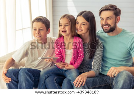 Beautiful young parents, their cute little daughter and son are watching TV and smiling, sitting on sofa at home. Girl is using a remote control - stock photo