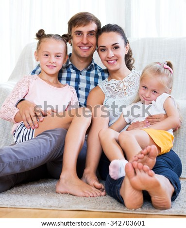 Beautiful young parents with two daughters relaxing at home