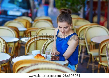 Beautiful young Parisian woman in blue tube top drinking coffee in an outdoor cafe and using tablet on a summer day - stock photo
