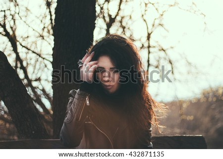 Beautiful young pensive woman sitting on a bench in park looking pensively and smoking cigarette - stock photo