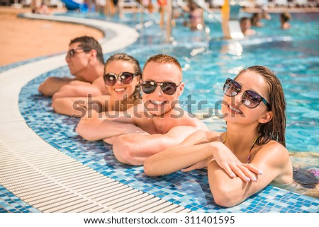 Beautiful young people having fun in swimming pool, smiling. - stock photo