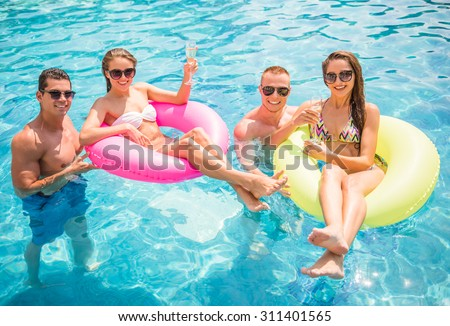 Beautiful young people having fun in swimming pool, smiling and drinking champagne. - stock photo