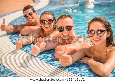 Beautiful young people having fun in swimming pool, smiling and showing thumbs up.