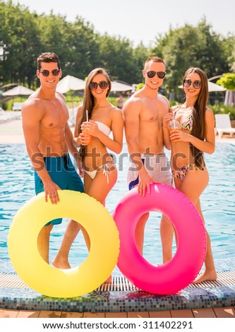 Beautiful young people having fun in swimming pool with colored rubber rings and cocktails. - stock photo
