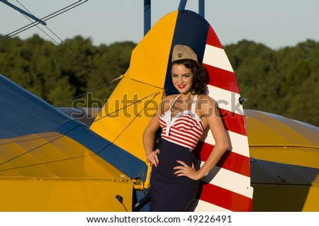 beautiful young pinup girl posing next to a vintage biplane aircraft - stock photo