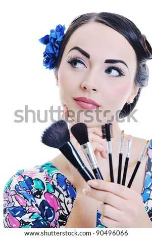 beautiful young pinup  woman apply makeup and cosmetics beauty treatment isolated on white in studio