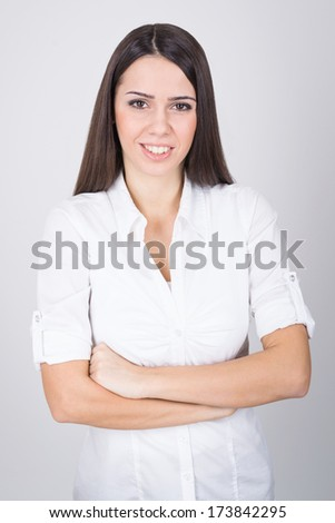 Beautiful young positive Caucasian brunette businesswoman in white shirt posing with arms crossed looking at camera against gray background. Business and causal natural real people concepts.