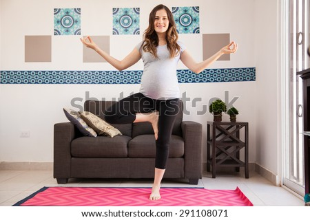 Beautiful young pregnant brunette doing some yoga poses in the living room - stock photo