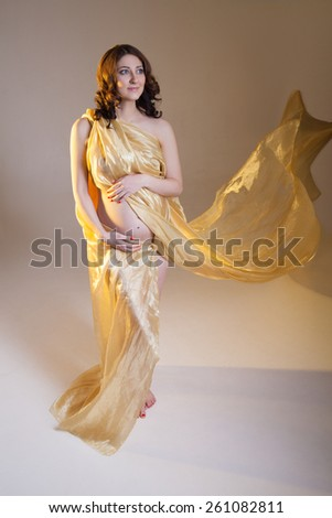 Beautiful young pregnant brunette woman with yellow transparent cloth in studio shot isolated on white background. Model is standing with her arms  on the belly.