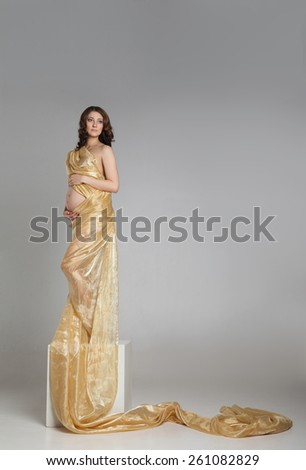Beautiful young pregnant brunette woman with yellow transparent cloth in studio shot isolated on white background. Model is standing as a statue on cube. - stock photo