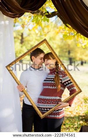 Beautiful Young Pregnant Couple Having Picnic in autumn Park. Happy Family Outdoor. Smiling Man and Woman relaxing in Park. Relationships.