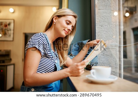 Beautiful young pregnant girl sitting in cafe reading magazine and drinking coffee with a croissant during vacation. - stock photo