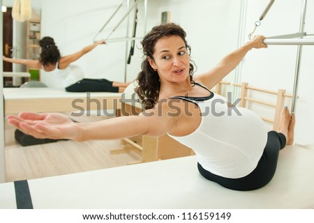 Beautiful young pregnant lady doing pilates in her last week before delivery. - stock photo
