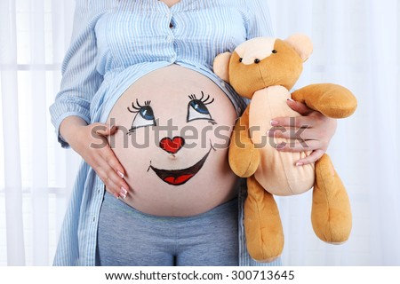 Beautiful young pregnant with baby toy  and picture on her belly, on light background - stock photo