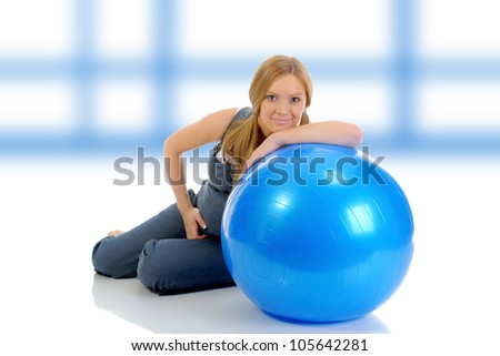 Beautiful young pregnant woman does sport exercises with a blue ball.