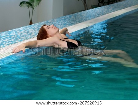 Beautiful young pregnant woman in a swimming pool  - stock photo