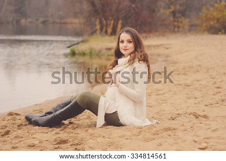 beautiful young pregnant woman in knitted cardigan walks outdoor, soft warm toned, cozy mood, soft focus - stock photo